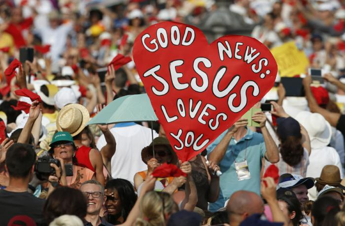 """A sign saying, """"Good news: Jesus Loves You,"""" is seen as Pope Francis arrives to greet participants in the Renewal of the Spirit meeting in St. Peter's Square at the Vatican July 3. (CNS photo/Paul Haring) See POPE-CHARISMATICS July 6, 2015."""